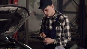 Técnico do serviço do carro que usa a tabuleta digital para examinar os indicadores de funcionamento principais do veículo Reparo video estoque