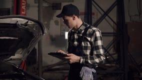 Técnico do serviço do carro que usa a tabuleta digital para examinar os interiores do veículo filme
