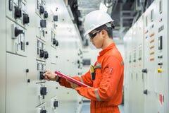 Técnico eléctrico y del instrumento que comprueba el tablero de control eléctrico de sistema el comenzar del motor en sitio de en foto de archivo libre de regalías