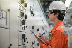Técnico eléctrico y del instrumento que comprueba sistemas de control eléctricos de proceso del petróleo y gas imagenes de archivo