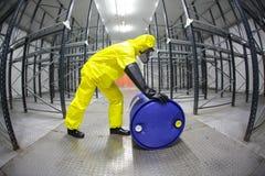 Técnico en el uniforme del amarillo que rueda el barril con la sustancia tóxica fotografía de archivo