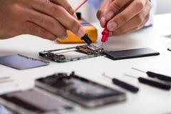 Técnico Examining Mobile Phone com multímetro digital imagem de stock royalty free