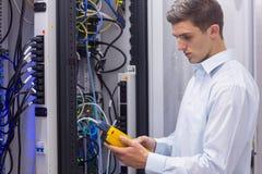 Técnico focalizado que usa o analisador digital do cabo em servidores Foto de Stock