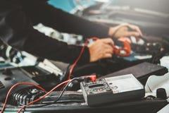 Técnico Hands del mecánico de coche que trabaja en batería de coche del servicio y del mantenimiento de reparación auto foto de archivo libre de regalías