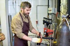 Técnico hermoso contento que pone la cerveza en botellas en la fábrica fotografía de archivo