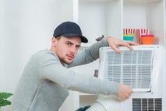 Técnico hermoso que instala el acondicionador de aire en el edificio fotografía de archivo libre de regalías