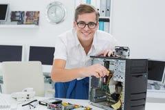 Técnico joven que trabaja en el ordenador quebrado Fotografía de archivo libre de regalías