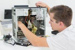 Técnico joven que trabaja en el ordenador quebrado Imagenes de archivo