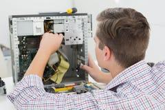 Técnico joven que trabaja en el ordenador quebrado Foto de archivo