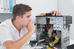 Técnico joven que trabaja en el ordenador quebrado Fotos de archivo