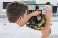 Técnico joven que trabaja en el ordenador quebrado Foto de archivo libre de regalías
