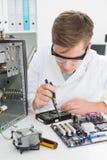 Técnico joven que trabaja en el ordenador quebrado Imagen de archivo