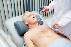 Técnico médico que une os elétrodos à caixa dos pacientes fotografia de stock