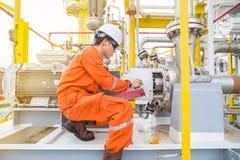 Técnico mecánico que comprueba y sistema lubricante de los datos de registración y del aceite de lubricante del motor eléctrico y fotos de archivo