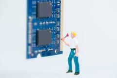 Técnico miniatura que elabora en el cierre de la RAM del ordenador Foto de archivo libre de regalías