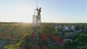 Técnico no polegar celular superior da mostra da antena acima no fundo do céu azul e da luz solar, tiro aéreo de vídeos de arquivo