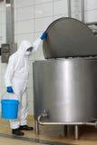 Técnico no uniforme branco com a cubeta que abre o tanque do processo industrial Imagens de Stock Royalty Free