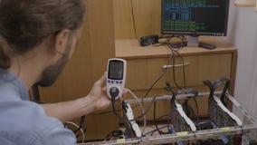 Técnico perito que usa uma monitoração do medidor de poder e indicando o consumo e o custo do equipamento da mineração do cryptoc vídeos de arquivo