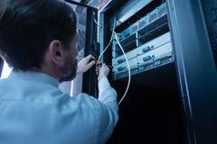 Técnico profesional elegante que fija el servidor de red imágenes de archivo libres de regalías