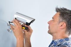 Técnico que ajusta la cámara CCTV foto de archivo libre de regalías