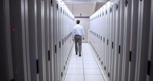 Técnico que camina en vestíbulo del servidor almacen de metraje de vídeo
