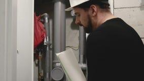 Técnico que comprueba el estado de los tubos de agua dentro almacen de metraje de vídeo