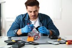 Técnico que comprueba smartphone quebrado en el taller de reparaciones imagenes de archivo