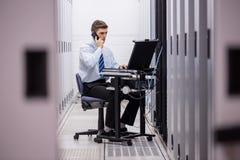 Técnico que fala no telefone ao diagnosticar servidores Imagens de Stock