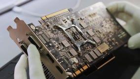 Técnico que fija una tarjeta de vídeo a la placa madre de una granja de computadora personal del bitcoin de la explotación minera almacen de video