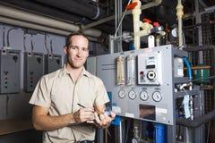 Técnico que inspeciona o sistema de aquecimento na caldeira Imagens de Stock Royalty Free