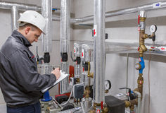 Técnico que inspeciona o sistema de aquecimento na sala de caldeira Fotos de Stock
