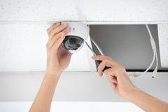 Técnico que instala a câmera do CCTV no teto dentro fotos de stock