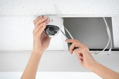 Técnico que instala la cámara CCTV en techo dentro fotos de archivo