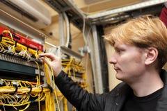 Técnico que prende o conector ótico fotografia de stock