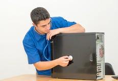 Técnico que repara el equipo de escritorio roto de la PC con el estetoscopio fotografía de archivo libre de regalías