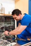 Técnico que repara el lavaplatos Fotografía de archivo libre de regalías