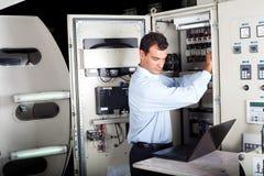 Técnico que repara la máquina automatizada Imágenes de archivo libres de regalías