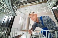 Técnico que repara a máquina de lavar louça Fotos de Stock