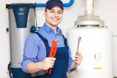 Técnico que repara um calefator de água quente foto de stock