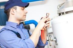 Técnico que repara um calefator de água quente imagem de stock