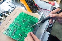 Técnico que repara una televisión. Foto de archivo libre de regalías