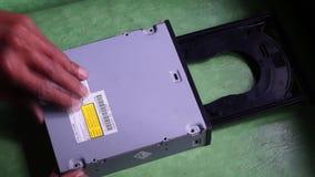 Técnico que saca la cubierta de la cubierta inferior de la unidad óptica del DVD almacen de video