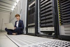 Técnico que se sienta en piso al lado de la torre del servidor usando el ordenador portátil Imagenes de archivo