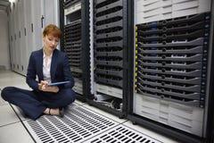 Técnico que se sienta en piso al lado de la torre del servidor usando la PC de la tableta Fotos de archivo libres de regalías