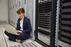 Técnico que senta-se no assoalho ao lado da torre do servidor usando o portátil Fotografia de Stock Royalty Free