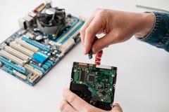 Técnico que tapa el serial de SATA EN el accesorio, cable de transmisión de Serial ATA en disco duro foto de archivo