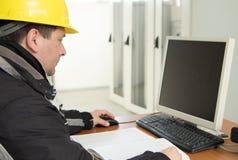Técnico que trabaja en el ordenador en Control-C de la central eléctrica Imágenes de archivo libres de regalías