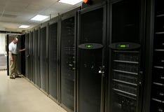 Técnico que trabaja en un cuarto del servidor Fotos de archivo libres de regalías