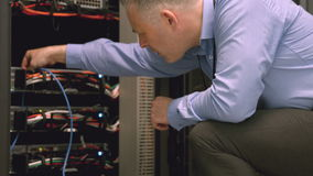 Técnico que usa el ordenador portátil para analizar el servidor almacen de metraje de vídeo
