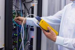 Técnico que usa o analisador digital do cabo em servidores Fotos de Stock Royalty Free
